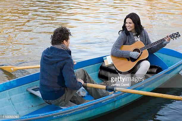 Fille jouant de la guitare dans la rangée bateau
