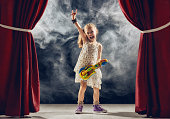 Cute little child girl playing guitar on stage. Kid dreams of becoming a rock musician.