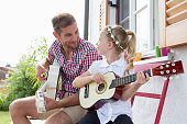 Girl playing guitar with father