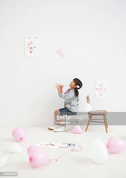 Girl playing heart-shaped balloons