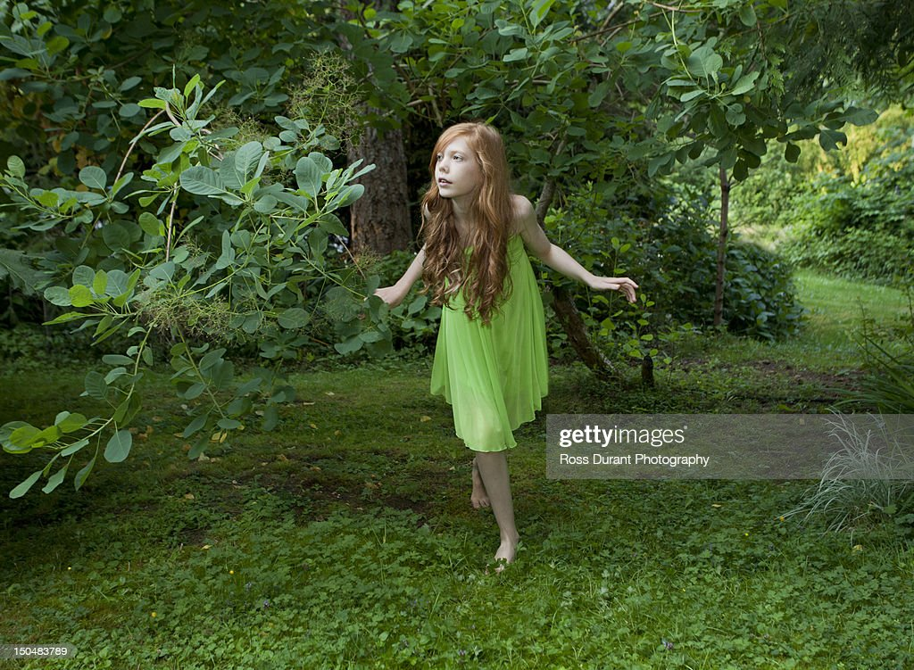 Girl playing hide and seek, seeking in a garden : Stock Photo