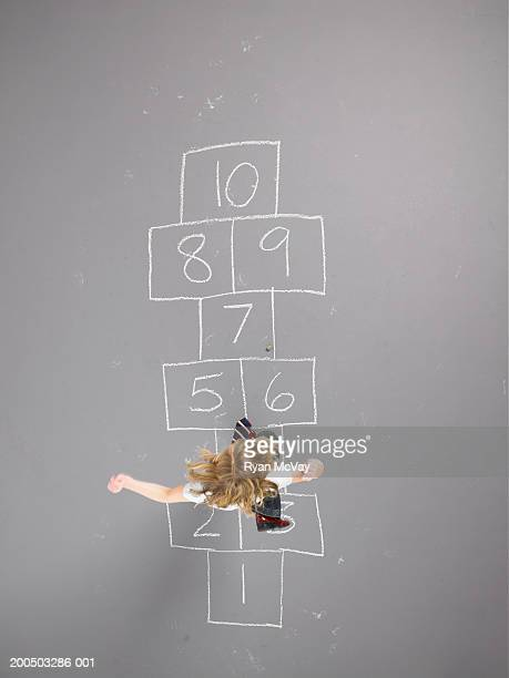 Girl (8-10) playing hopscotch, overhead view