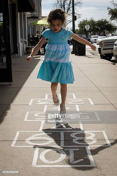 Girl playing hopscotch.