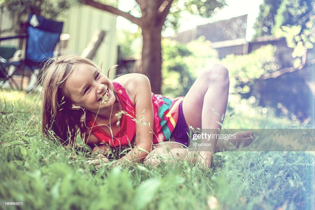 girl playing in her yard and listening to MP3 player : Stock Photo