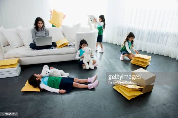 Girl Playing in Living Room While Mother Using Laptop Computer