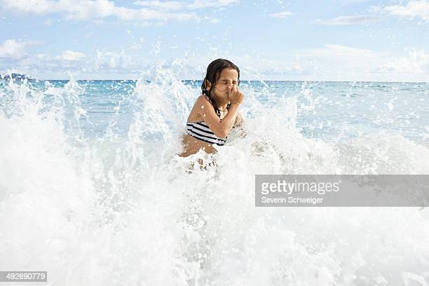 Girl playing in sea, holding nose