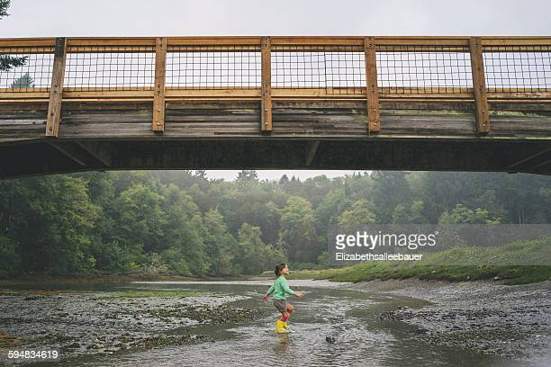 Girl playing in shallow water under bridge
