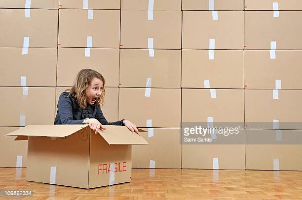 Girl playing inside a cardboard box