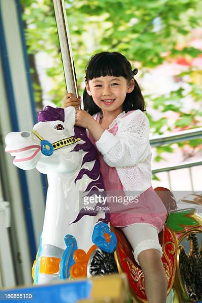 A girl playing merry-go-round outside