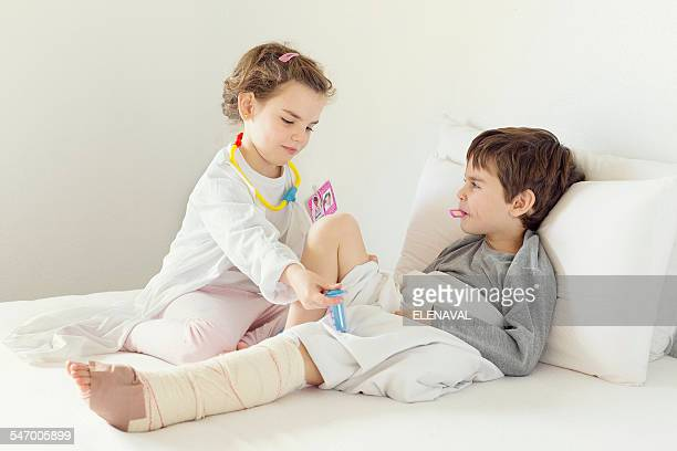 Girl playing nurse to her brother in bed