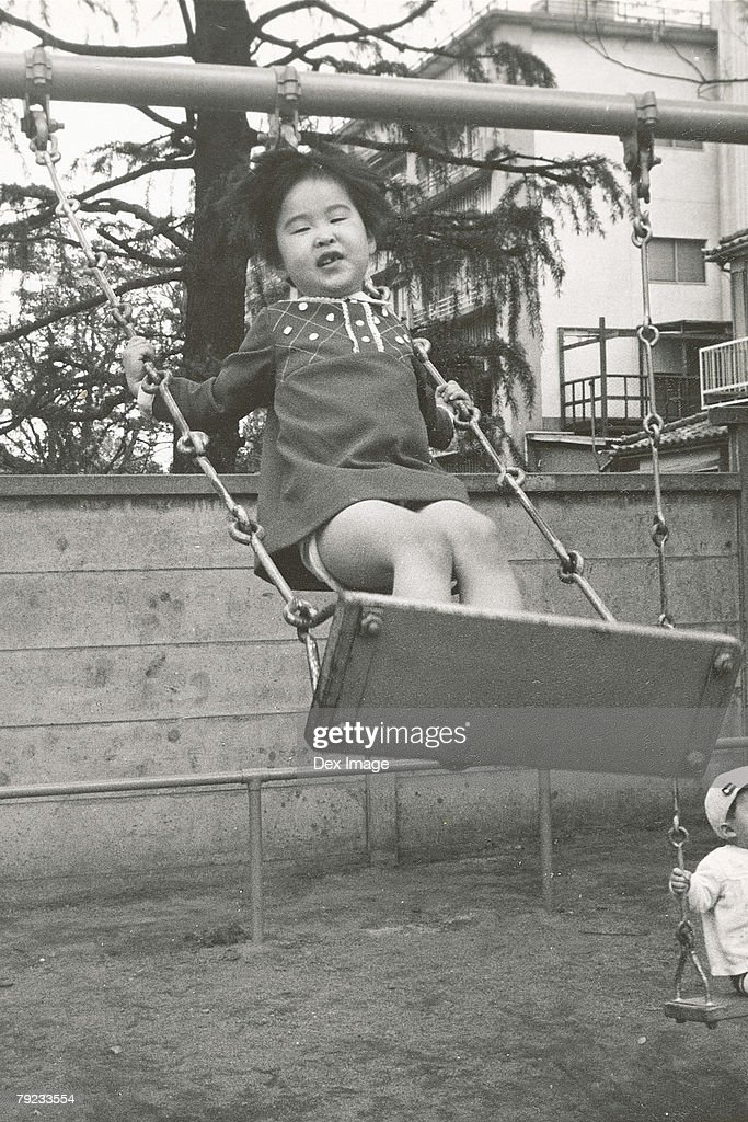 Girl playing on a swing : Stock Photo