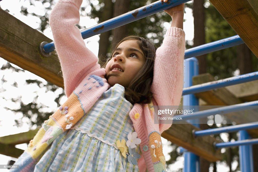 girl playing on monkey bars : Stock Photo