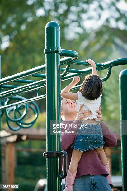 Girl playing on monkey bars.