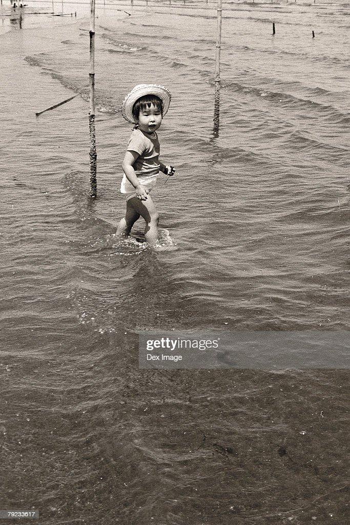 Girl playing on river bank : Stock Photo