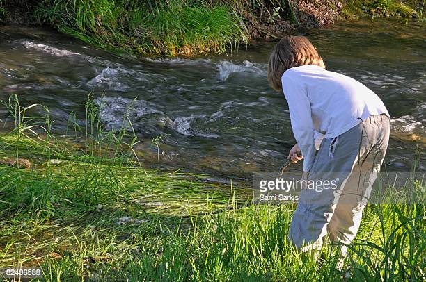 Girl (7-8) playing on river's bank