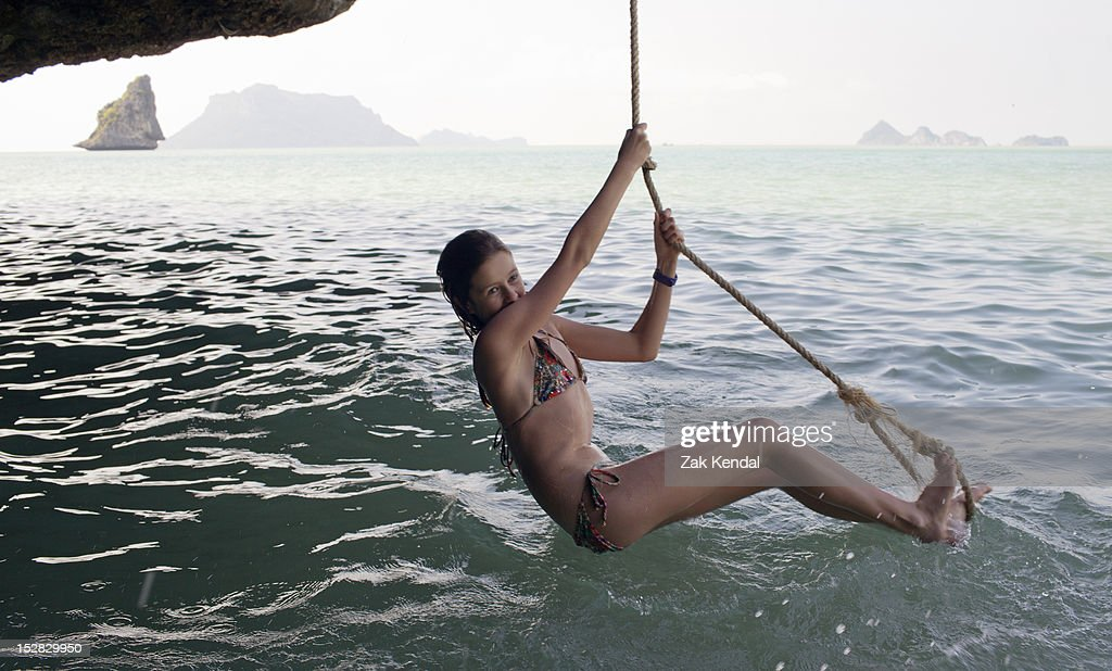 Girl playing on rope over water