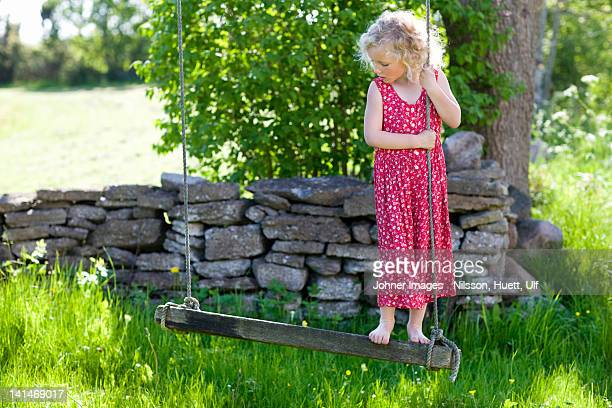 Girl playing on rope swing in field