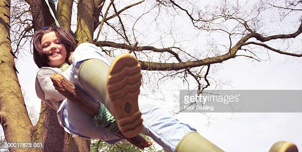 Girl (7-9) playing on rope swing, low angle view