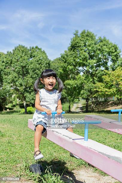 Girl Playing On Seesaw