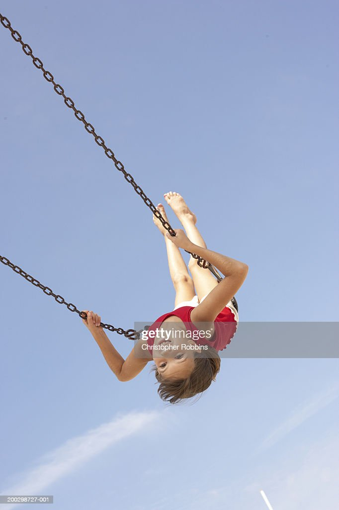 Girl (8-10) playing on swing, swinging upside down, portrait : Stock Photo