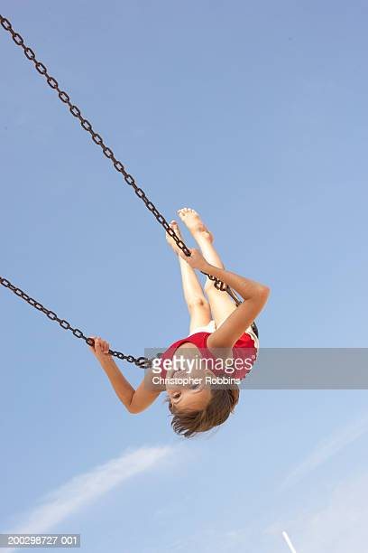 Girl (8-10) playing on swing, swinging upside down, portrait