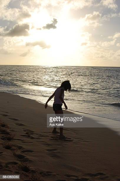 A girl playing on the beach in Hawaii sunset