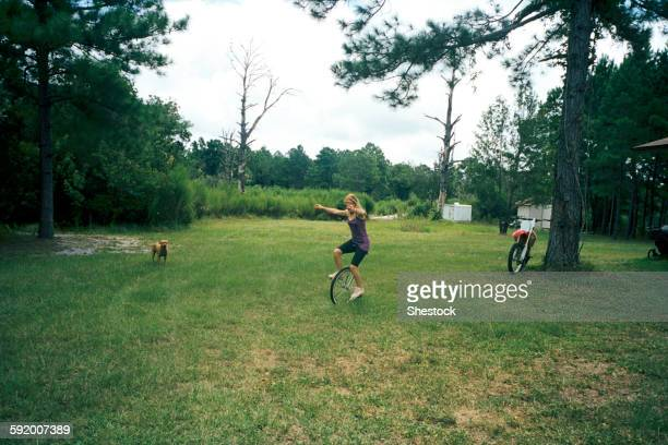 Girl playing on unicycle in field