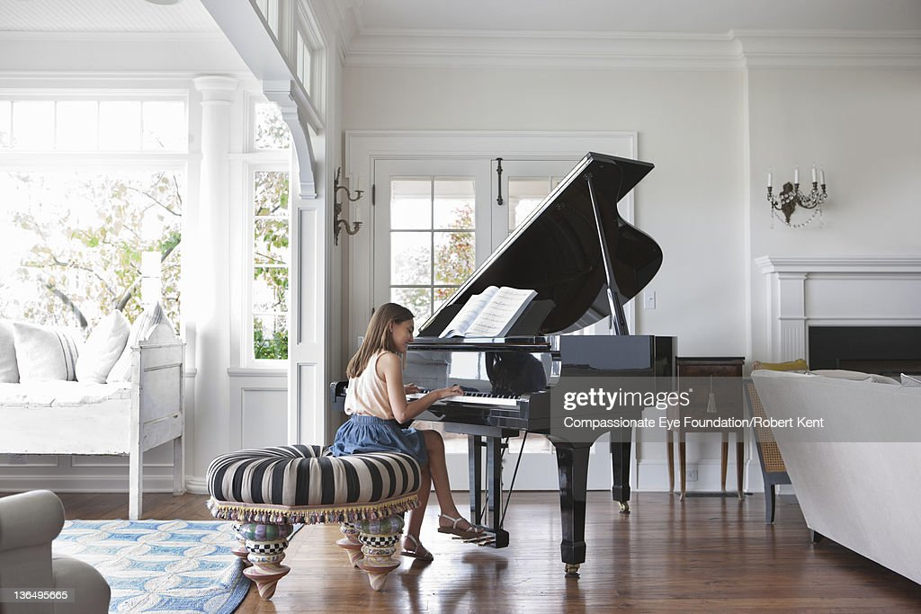 Girl (10-11) playing piano in living room : Stock Photo