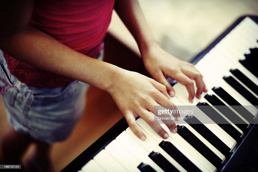 Girl playing piano : Stock Photo