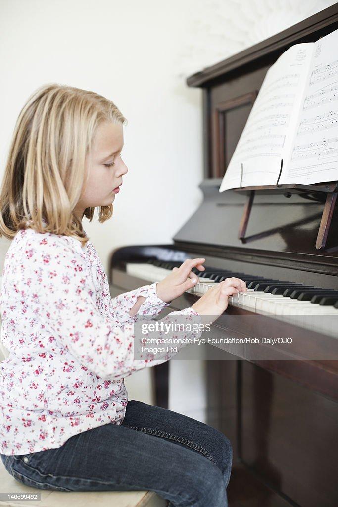 Girl (7-8) playing piano : Stock Photo