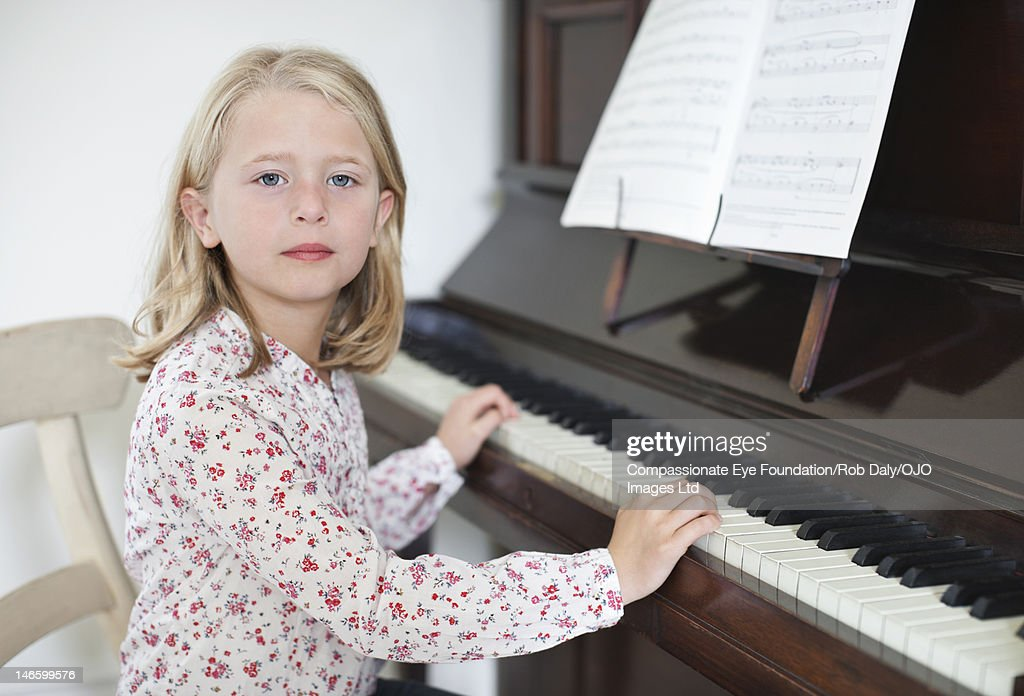 Girl (7-8) playing piano : Stock Photo
