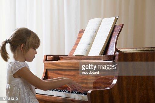 Girl (5-6) playing piano : Foto de stock
