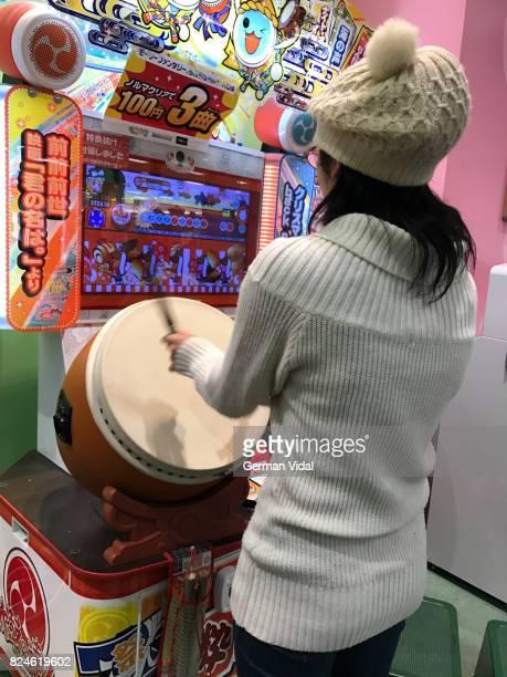 Girl playing Taiko no Tatsujin arcade game, Japan