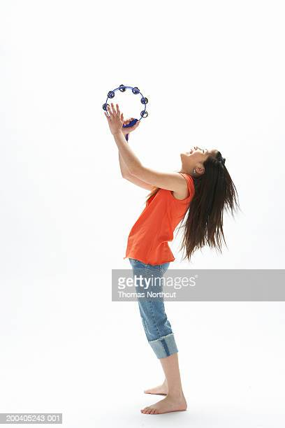 Girl (9-11) playing tambourine, head back, side view