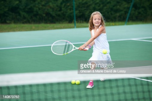 Girl playing tennis on court