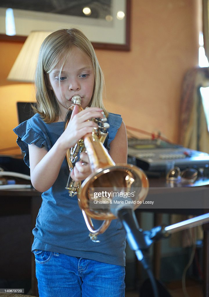 Girl playing trumpet into microphone : Stock Photo