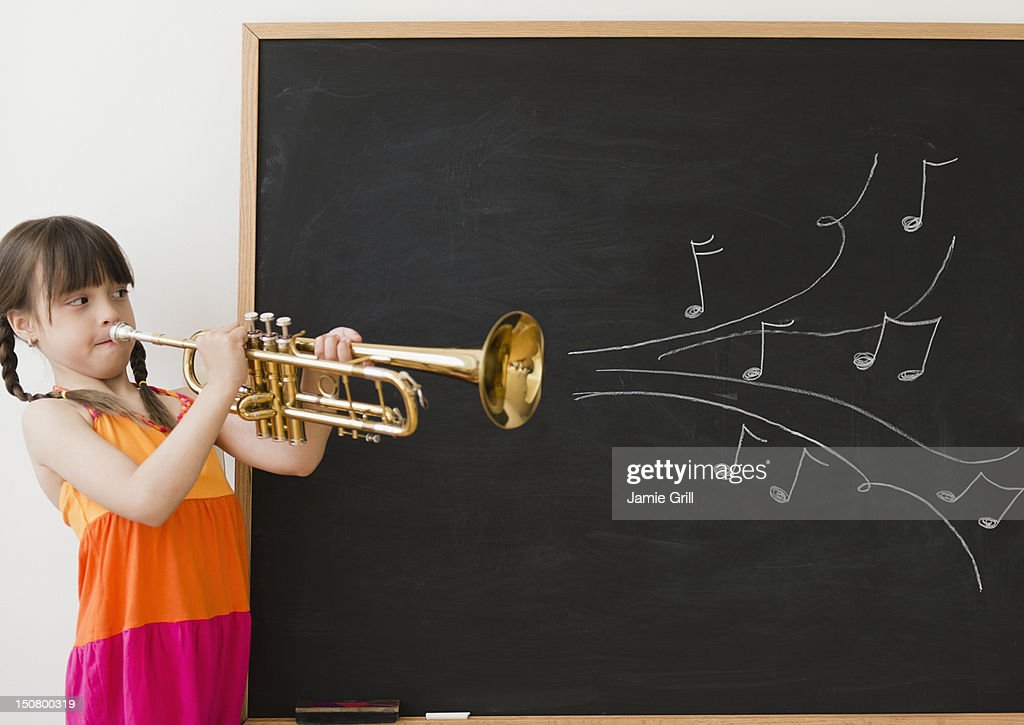 Girl playing trumpet, musical notes coming out