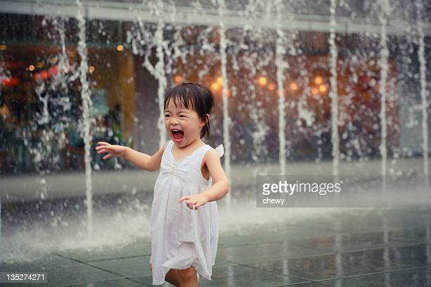 Girl playing under fountain water
