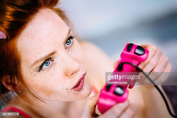 Girl playing video game with pink controller