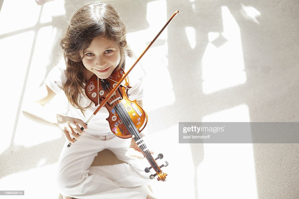 Girl playing violin on carpet : Stock Photo