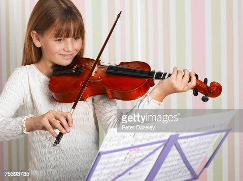 Girl (8-9) playing violin, smiling : Stock Photo