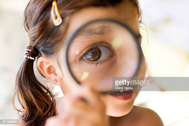 A girl playing with a magnifying  glass
