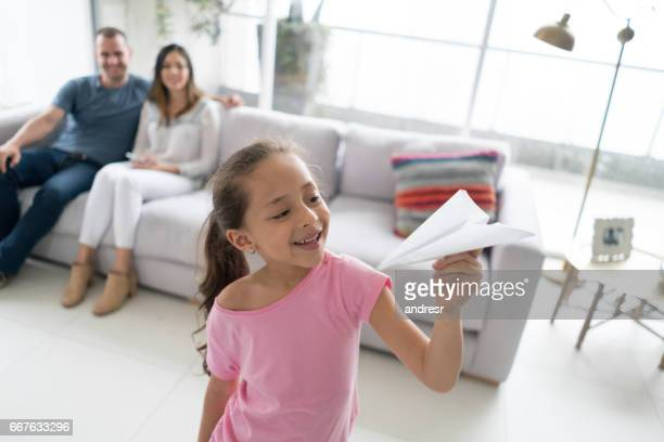 Girl playing with a paper plane at home