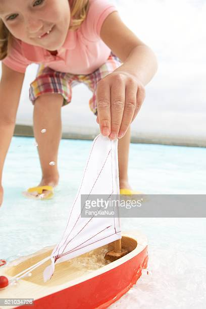 Girl playing with a toy sailboat