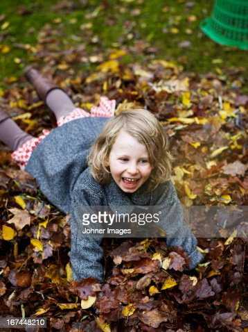 Girl playing with autumn leaves : Stock Photo