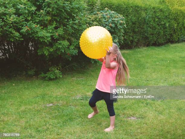 Girl Playing With Ball While Standing On Grassy Field At Park