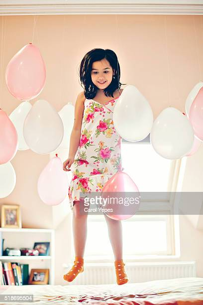 girl playing with balloons at home