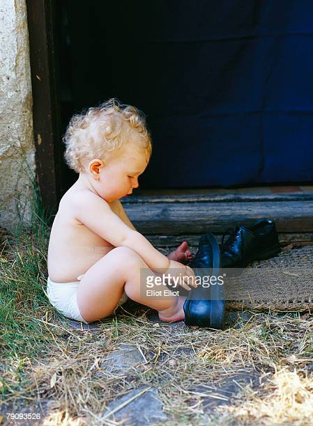 A girl playing with big shoes.