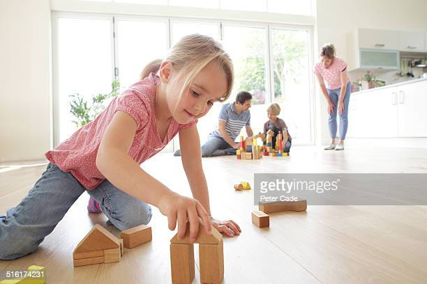 girl playing with blocks family in the back ground