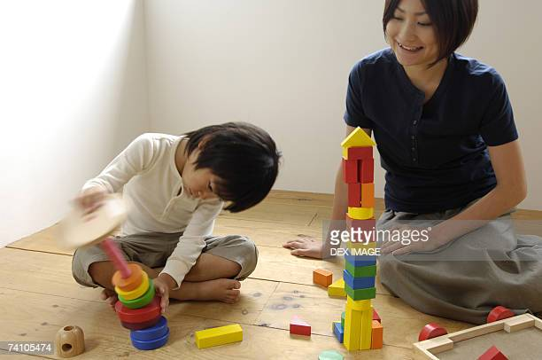 Girl playing with blocks with her mother looking at her